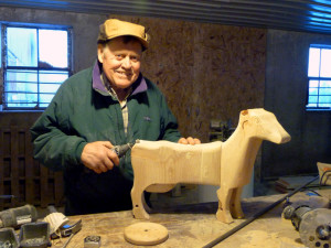Schroeder said he delights in shaping the cow kiddie carts from raw wood into finished products. Photo by Jim Massey